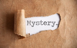 Uncovering a mystery. Torn piece of scroll uncovering mystery Stock Photo