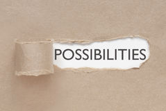 Uncovering possibilities. Torn paper revealing the word possibilities Royalty Free Stock Photography