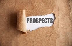 Uncovering prospects. Torn piece of scroll uncovering prospects underneath stock photo