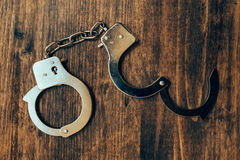 Uncuffed, open hand cuffs on wooden desk, top view Royalty Free Stock Image