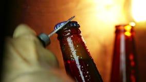 Uncup d'homme une bouteille de bière avec la mousse avec des baisses gelées de glace, sur le fond d'or, l'amusement et la nutriti banque de vidéos