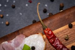 Uncured Apple Smoked Bacon garnished with Green Scallions, dried Red Chile Pepper, Garlic and Rainbow  Peppercorns. On natural wooden cutting board royalty free stock photography