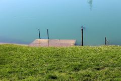 Uncut grass covered river bank with small flooded concrete pier with metal steps. On warm sunny day stock images