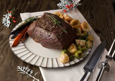 Uncut Roast Beef With Yorkshire Puddings. Uncut piece pf peppercorn roast beef with herbed Yorkshire puddings garnished with roasted vegetables Royalty Free Stock Photography