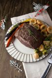 Uncut Roast Beef With Yorkshire Puddings. Uncut piece pf peppercorn roast beef with herbed Yorkshire puddings garnished with roasted vegetables Royalty Free Stock Images