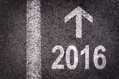 2016 und ein Pfeil geschrieben auf eine Asphaltstraße Lizenzfreie Stockfotografie