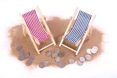 1 und 2 Euromünzen liegen vor Spielzeugstrandstühlen Stockfotos