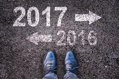 2017 und 2016 geschrieben auf einen Asphaltstraßehintergrund Lizenzfreies Stockbild
