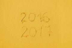 2016 und 2017 geschrieben auf Sand am Strand in gelbe Farben Lizenzfreies Stockfoto