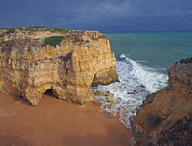 Und Strand mit Sandsteinklippen und ein blauer Ozean und ein Himmel Lizenzfreies Stockfoto