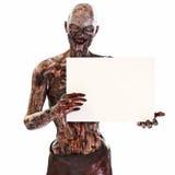 Undead del zombi que sostienen una tarjeta en blanco de la muestra del anuncio en un fondo blanco aislado con el sitio para el es fotos de archivo