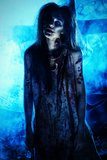 Undead girl. Bloodthirsty zombi standing at the night cemetery in the mist and moonlight Royalty Free Stock Image