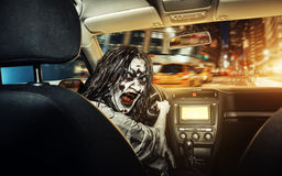 Undead girl with bloody face rides in the car stock image