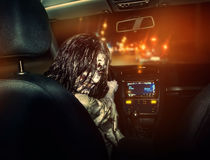 Undead girl with bloody face rides in the car royalty free stock images