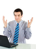 Undecided businessman. Looking to the laptop and raising his hands Royalty Free Stock Photo