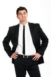 Undecided businessman. A picture of a young handsome undecided businessman standing over white background Stock Image