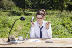 Undecided businesswoman does not know which phone to pick up Royalty Free Stock Photography