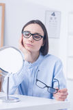 Undecided client choosing eyeglasses. Undecided client in front of mirror, choosing new eyeglasses Royalty Free Stock Photo