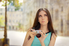Undecided Girl with Compact Digital Camera Stock Images