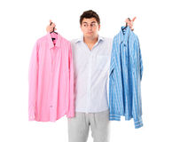 Undecided man. A portrait of an undecided man trying to choose between two shirts over white background Royalty Free Stock Photos