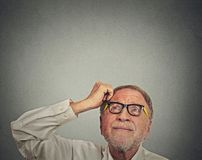 Undecided man with glasses scratching head thinking looking up Stock Images