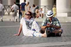 Undecided tourists couple looking at a guide book. A tourist couple is undecided about which route to take in Rome (Italy) / He studied the guide and she waits Royalty Free Stock Images