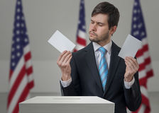 Undecided voter holds envelopes in hands above vote ballot. Undecided voter holds envelopes in hands above vote ballot and making decision. Election in USA Royalty Free Stock Photography