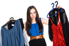 Undecisive young woman choosing which dress to wear Royalty Free Stock Photo