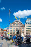 Undefined people cross the street on bikes on Dam Square, De Bijenkorf flagship store on the background on April 30, 2015. AMSTERDAM-APRIL 30: Undefined people Stock Photos