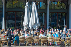 Undefined people have drinks in outdoor cafe with Rembrandtplein view. Stock Images