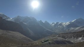 Undefined trekkers walking on trekking trail in Nepal. With Panoramiv View of Mountains near Thorung La Pass stock footage