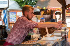 An undefinite male person on the sausage market working and serving fresh cooked food Stock Images