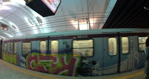 Undeground train with graffiti leaving station. ROME, ITALY - FEBRUARY 12, 2015: Wide angle shot of subway train decorated with bright graffiti leaving the stock video footage