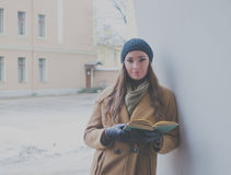 Under the arch near the wall a beautiful girl book. Beautiful girl with a book leaned on the wall arch in winter Stock Images