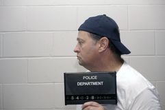 Under arrest. Man has his photo taken while being booked for a criminal offense stock image