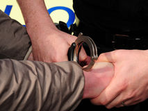 Under arrest. Handcuffs going on. A suspect is detained and cuffed by a police officer Royalty Free Stock Photography
