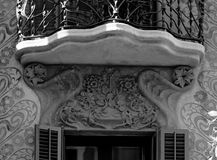 Under the balcony there are some flowers. Shot in black and white and apinted in colors detail on the sculpture on the facade of this historic building Royalty Free Stock Images