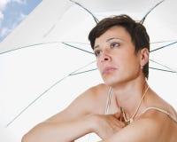 Under a beach umbrella. Beautiful woman under a beach umbrella Royalty Free Stock Photography