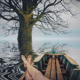 Under the big oak tree. Man on vacation, resting in a wooden boat under the big oak tree on a autumn lake Stock Images
