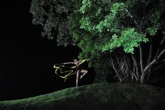 Asian girl dancing ballet under big tree at night. Under the big tree at night, Asian girls dancing ballet, charming night, open-air stage, close to nature royalty free stock photography