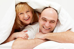 Under blanket. Happy woman lying on the husband under blanket Royalty Free Stock Images
