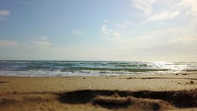 Under the blue sky the waves roll in on the beach. Under the blue sky with soft white clouds the waves roll in on the sandy beach stock footage
