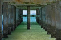 Under the boardwalk. Looking towards the blue sea from underneath the boardwalk Stock Photo
