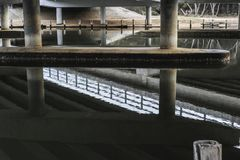 Under the boardwalk or bridge showing wonderful reflections of this capture. Bridge with reflections on calm river water royalty free stock photos