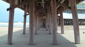 Under the boardwalk Daytona Beach. Motion video walking under the boardwalk pier at Daytona Beach FL stock footage