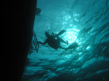 Under the boat. Diver returning to dive-boat Stock Images