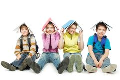 Under books. Educational theme: group of teenagers sitting together and holding books on their heads Stock Photo