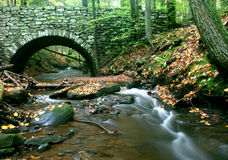 Under the Bridge. Wooded Brook flowing under stone bridge stock photos