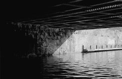 Under the Bridge. Monochrome film type image of light and shade under a bridge spanning an urban canal Royalty Free Stock Image