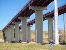 Under the bridge. Man walking under high freeway bridge stock photo